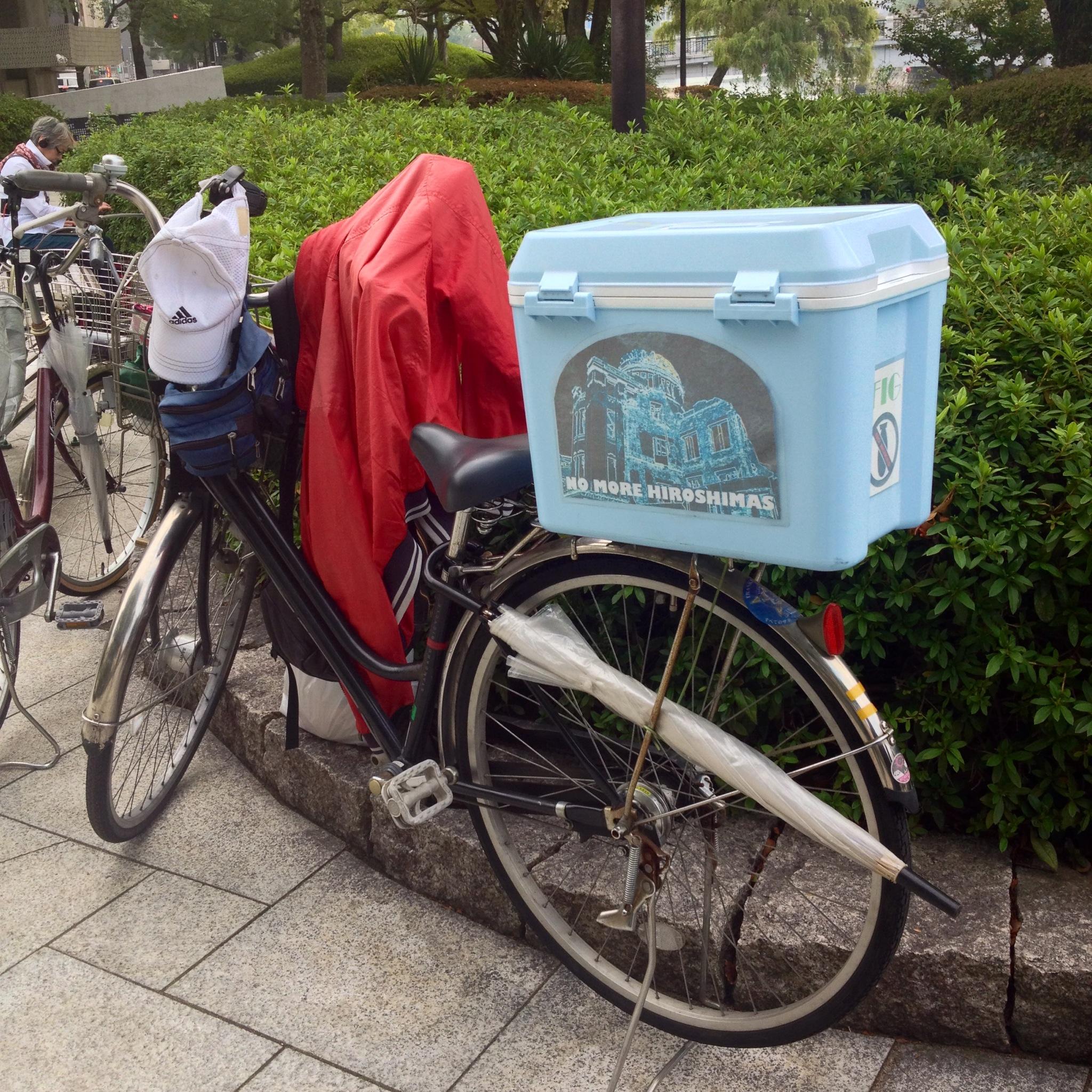 """La bici dell'uomo degli origami, sul suo bauletto la scritta """"No more Hiroshimas"""""""
